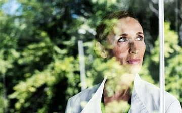 Kvinna fotograferad genom fönster med reflektion av gröna träd i fönstret